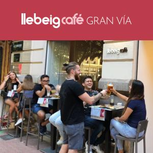 Clientes brindando con pintas de cerveza en una de las terrazas de Llebeig Café